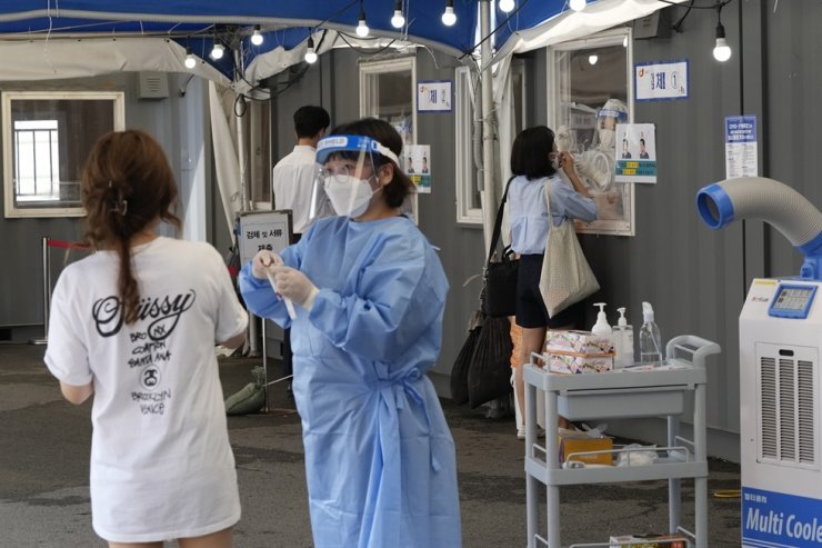 Medical workers takes nasal samples from residents for coronavirus tests at a makeshift testing site in Seoul, July 20. AP-Yonhap