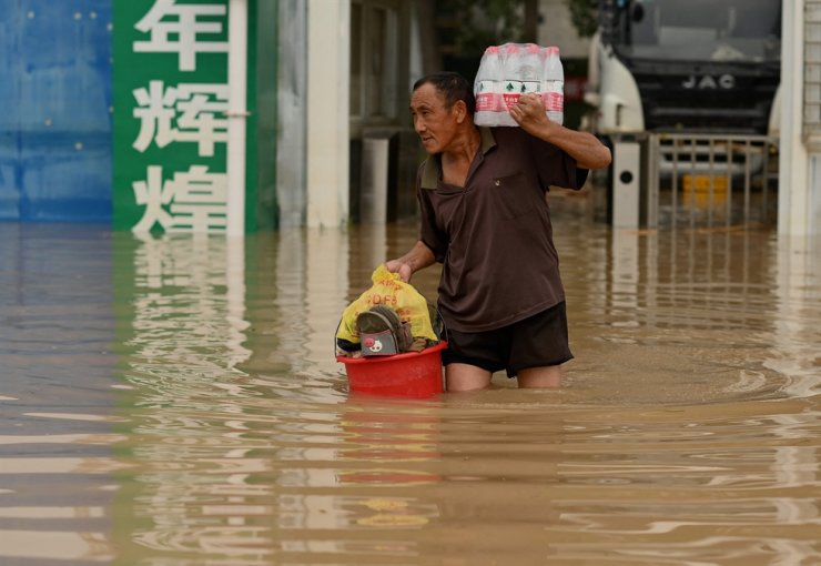 A man carries bottled water across a flooded street, July 23, following heavy rain that flooded and claimed the lives of at least 33 people in the city of Zhengzhou, in China's Henan Province earlier in the week. AFP-Yonhap