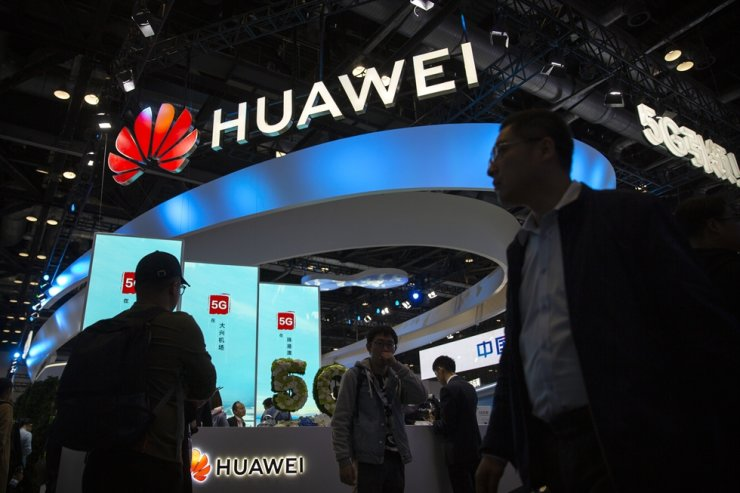 Attendees walk past a display for 5G services from Huawei at the PT Expo in Beijing, Oct. 31, 2019. AP-Yonhap