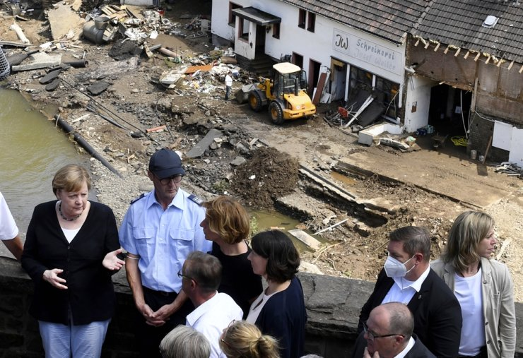 German Chancellor Angela Merkel, left, and the governor of the state of Rhineland-Palatinate, Malu Dreyer, rear third left, are seen on a bridge in Schuld, during their visit in the flood-ravaged areas to survey the damage and meet survivors, Germany, July 18. AP-Yonhap