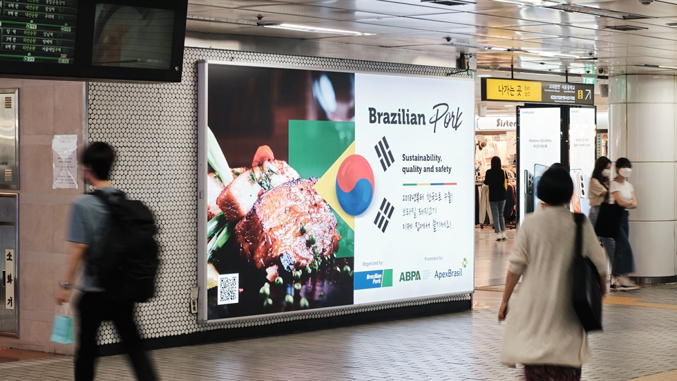 Brazilian Ambassador to Korea Luis Henrique Sobreira Lopes, center, and Brazilian Agricultural Attache Gutemberg Barone, point at digital screens that have images promoting Brazilian pork and chicken in a Seoul subway station. Courtesy of the Embassy of Brazil