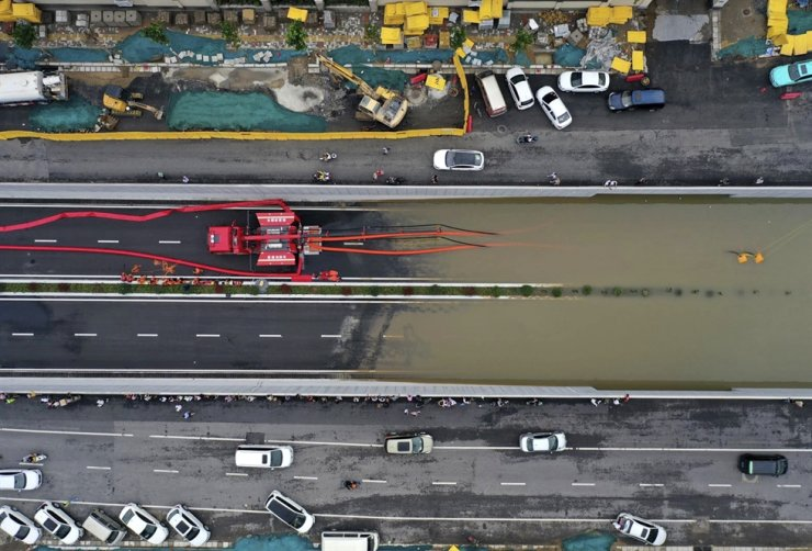 In this aerial photo released by Xinhua News Agency, firefighters pump rainwater from a road underpass in Zhengzhou in central China's Henan province, July 21. AP-Yonhap