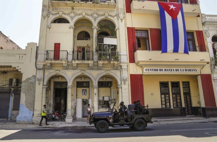 Police patrol the streets as they drive past a large Cuban flag hanging from the facade of a building, Havana, Cuba, July 21. AP-Yonhap
