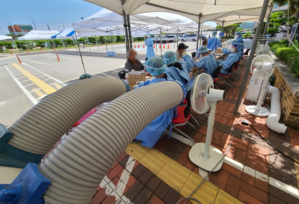 People line up for COVID-19 diagnostic tests at a makeshift testing center in front of Seoul Station, Sunday. Yonhap