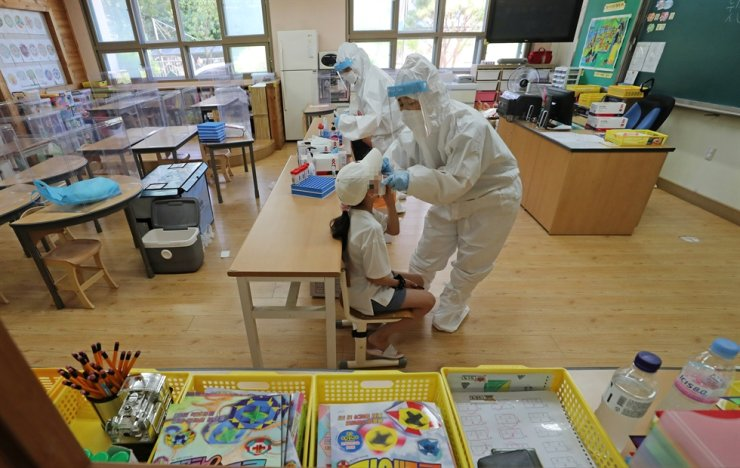 Medical workers conduct COVID-19 testing at a temporary testing center installed at an elementary school in Daejeon, Thursday. Yonhap