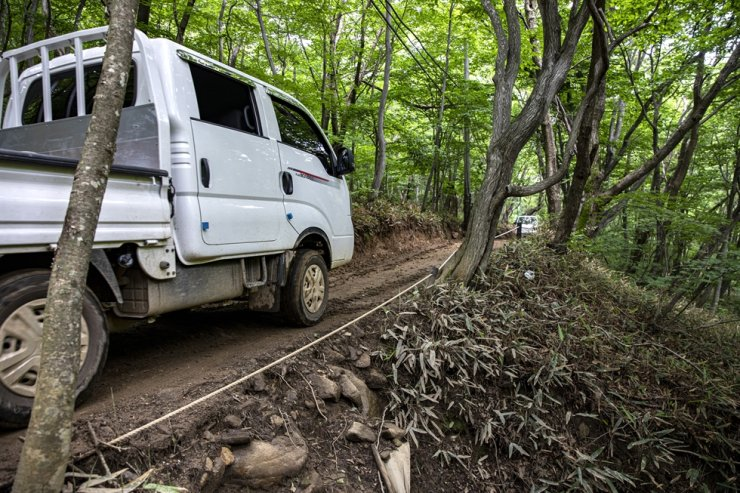 Park So-hee's pickup truck is parked on the trail stretching from Seolpi Village parking lot to Park's guesthouse at the end of Gombaeryeong mountain pass on July 13. Located downhill from the trail is a rocky mountain creek (not seen in this photo). Korea Times photo by Shim Hyun-chul