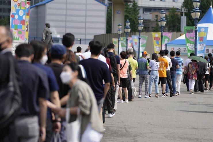 People queue in line to wait for coronavirus testing at a coronavirus testing site in Seoul, July 7. AP-Yonhap