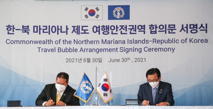 Vice Transport Minister Hwang Seong-kyu, right, signs a travel bubble agreement with Saipan's governor, Ralph Torres, in Seoul on June 30. Yonhap