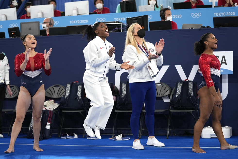 Simone Biles, center, of the USA hugs her teammates Sunisa Lee, left, while Grace McCallum looks on after competing on the Uneven Bars during the Women's Qualification of the Tokyo 2020 Olympic Games Artistic Gymnastics events at the Ariake Gymnastics Center in Tokyo, Japan, 25 July 2021. EPA-Yonhap