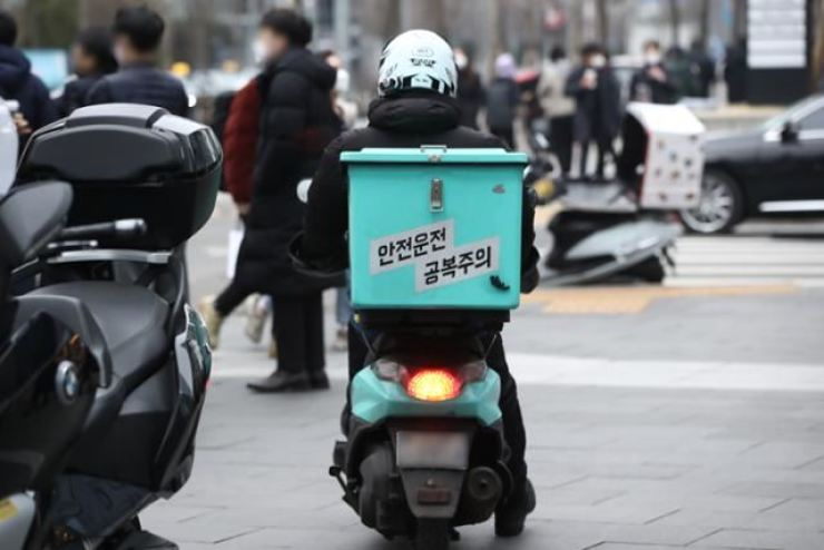 A Baedal Minjok delivery worker rides a scooter to deliver food in Seoul on Jan. 3. Korea Times file