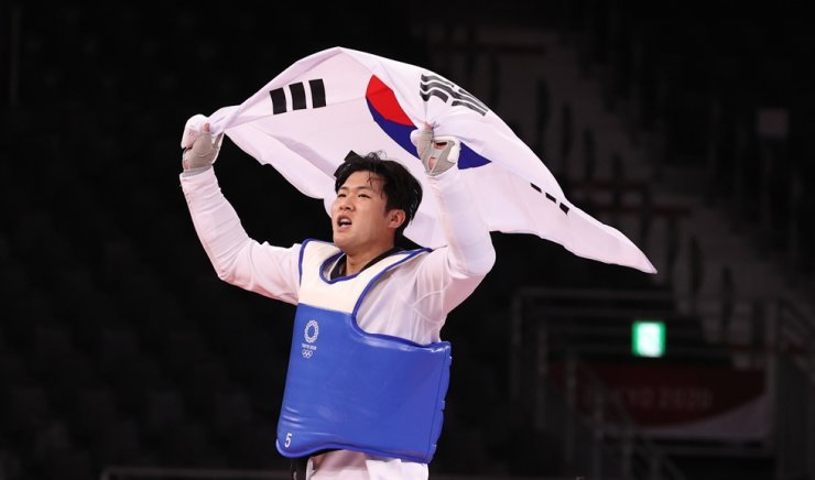 In Kyo-don holds Korean national flag after winning bronze medal in men's taewondo at Makuhari Messe Hall A in Chiba, Tokyo, Tuesday. Yonhap
