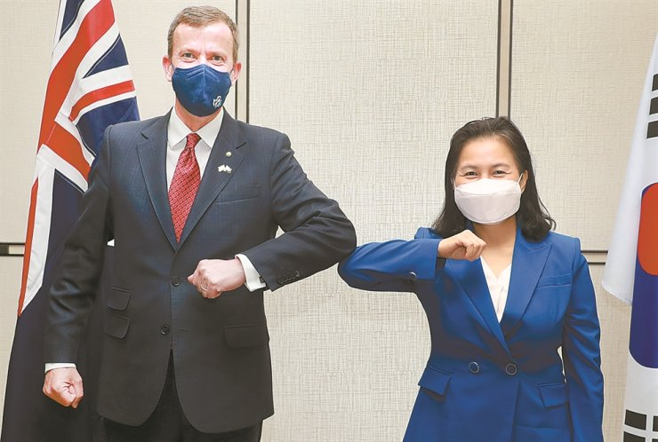 Trade Minister Yoo Myung-hee bumps elbows with her Australian counterpart Dan Tehan, ahead of their meeting at the Four Seasons Hotel Seoul, Monday. The two ministers agreed on stronger cooperation for investments into and development of mineral resources including rare earth elements. Yonhap