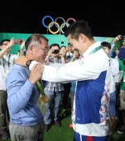 South Korean archer Ku Bon-chan, right, hangs a gold medal around Korea Archery Association President Chung Euisun's neck after winning the men's individual event, at the Rio Olympics in Brazil in 2016. Yonhap