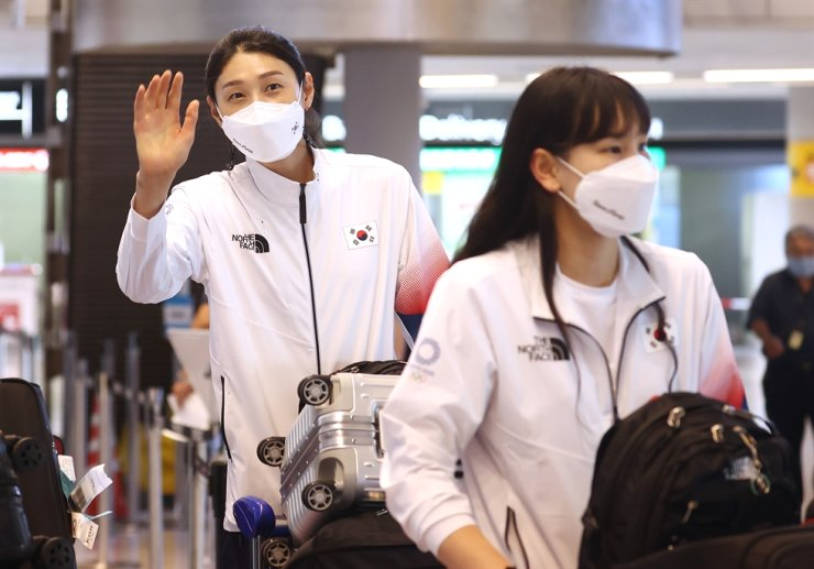 Kim Yeon-koung, left, captain of Korea's female volleyball national team, waves her hand after arriving at Narita International Airport in Japan, July 20. Yonhap