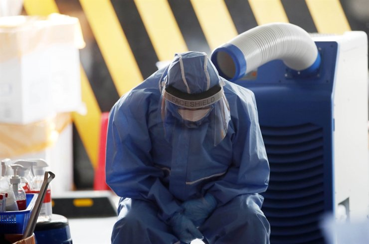 A medical worker cool the heat in front of a cooler at a COVID-19 testing center in Gwangju, Thursday. Yonhap