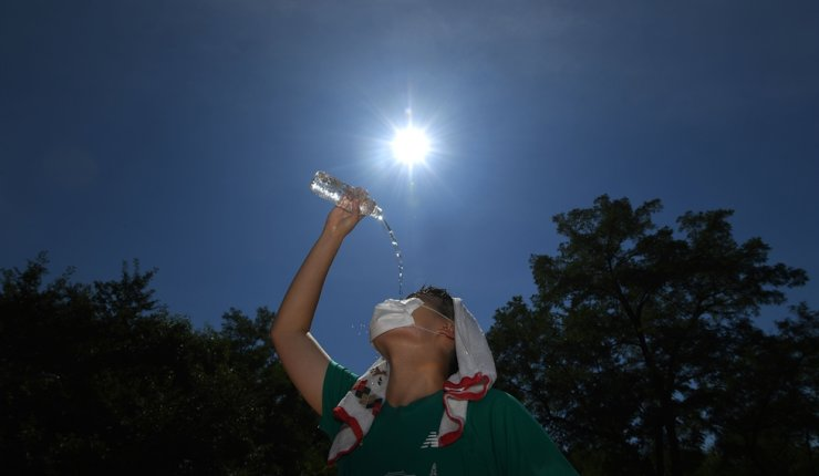 A teenager tries to cool himself down with water at a basketball court in Dongdaegmun District, Seoul, as the temperature rose to 35 degrees Celsius, July 22. Korea Times file