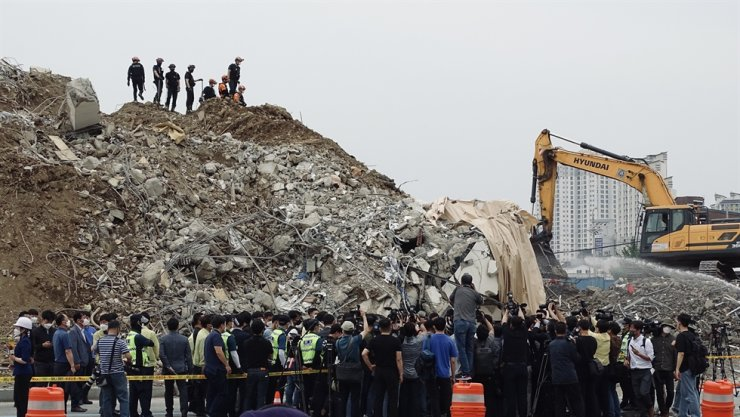 The day after nine people died when a building collapsed during demolition, a press conference is held at the site in Gwangju while emergency workers stand atop the wreckage, June 10. / Courtesy of Isaiah Winters