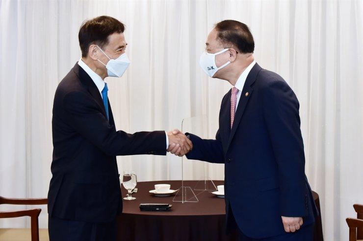 Bank of Korea Gov. Lee Ju-yeol, left, and Finance Minister Hong Nam-ki shake hands at the Press Center in central Seoul, July 2. Yonhap