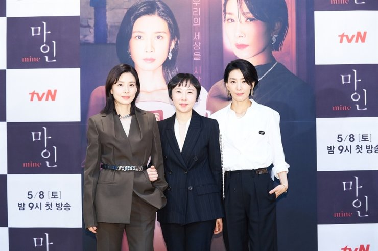 In file photo from May, actress Lee Bo-young, from left, director Lee Na-jeong, and actress Kim Seo-hyung pose for pictures during a media conference for 'Mine.' Courtesy of tvN