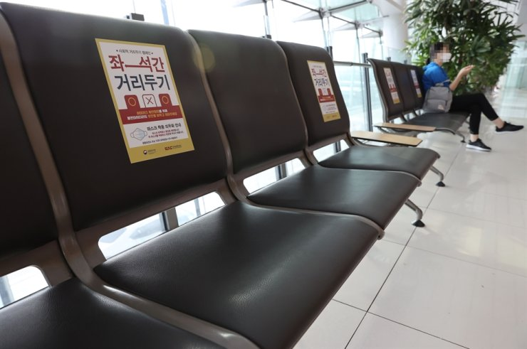 Social distancing signs are seen on benches at Gimpo International Airport in Seoul, July 9. Yonhap