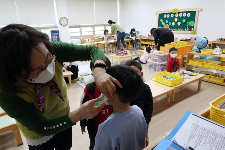A teacher checks a child's temperature at a public kindergarten in Gwangju in this April 3, 2020 photo. Yonhap
