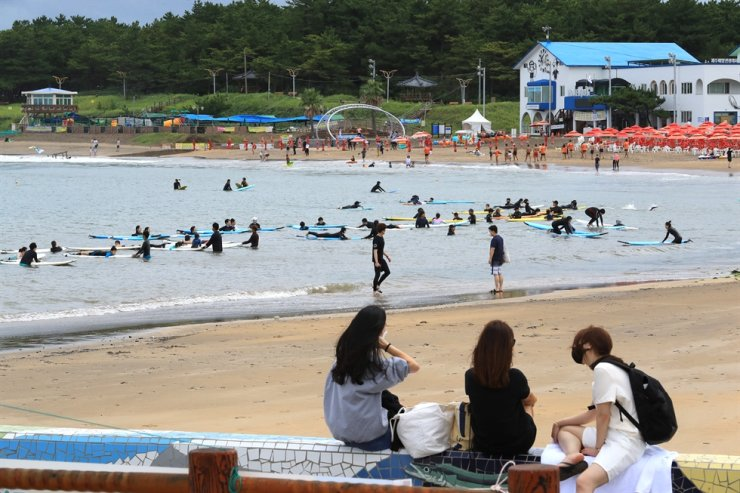 Vacationers enjoy surfing at a beach on Jeju Island, Monday. Yonhap