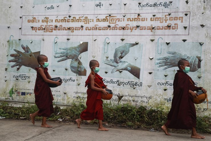 Buddhist novice monks wearing face masks walk past a COVID-19 awareness sign as they collect morning alms in Yangon, Myanmar, July 15. AP-Yonhap