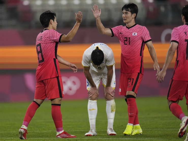 South Korea's Lee Kang-in, left, celebrates with his teammate Kim Jin-gyu, right, after scoring his side's fourth goal as Tudor Baluta of Romania, center, looks down during a men's football match at the 2020 Summer Olympics in Kashima, Japan, Sunday. / AP-Yonhap