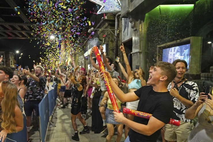 People celebrate as they queue up for entry at the Viaduct Bar in Leeds, after the final legal coronavirus restrictions were lifted in England at midnight, July 19. AP-Yonhap