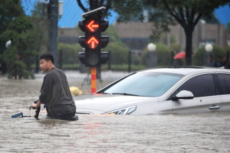 A man rides a bicycle through a flooded intersection in Zhengzhou in central China's Henan Province, July 20. AP-Yonhap