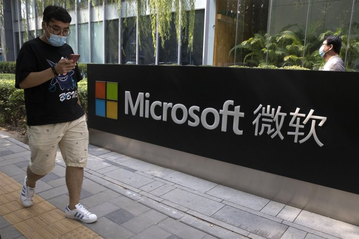In this Aug. 7, 2020, file photo, a man looks at his smartphone as he walks by the Microsoft office in Beijing. The Biden administration on July 19 blamed China for a hack of Microsoft Exchange email server software that compromised tens of thousands of computers around the world earlier this year. AP-Yonhap