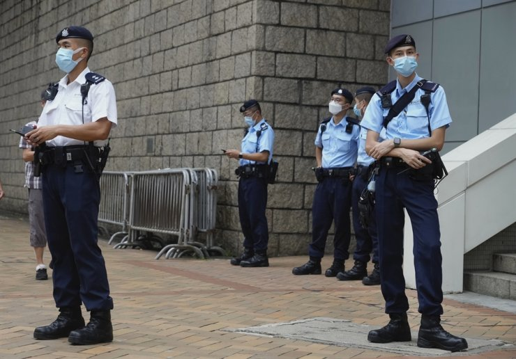 Police officers stand guard as they wait for Tong Ying-kit to leave a court in Hong Kong, July 27. Tong, 24, the first person to be tried under Hong Kong's sweeping national security law was found guilty of secessionism and terrorism on Tuesday in a ruling condemned by human rights activists. AP-Yonhap