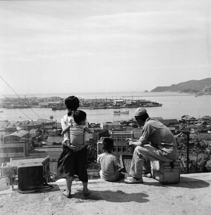 Adults and children overlook a harbor town, sometime between 1956 and 1959. / Courtesy of Susan Hanley