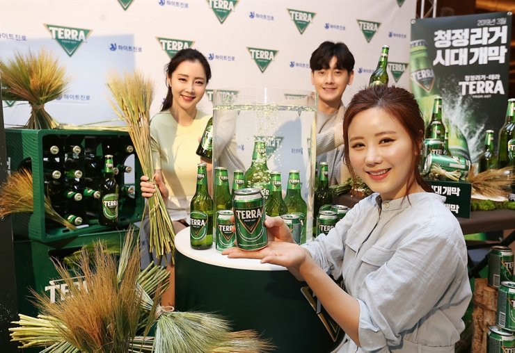 Models hold Terra beer products in this commercial image shared by HinteJinro on July 27. Courtesy of HiteJinro