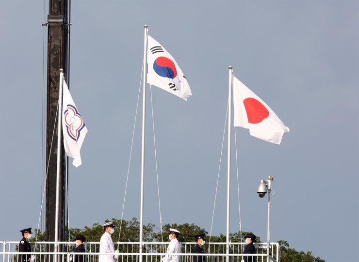 The flag of 'Chinese Taipei' (Taiwan), left, is seen during the medal ceremony for the men's archery event at the Yumenoshima Park Archery Field in Tokyo, Monday. The flag features a small white sun superimposed on a blue circle ― a symbol pulled from Taiwan's national flag ― and the five Olympic rings, encircled by a blue Asian plum blossom, on a white background. Yonhap