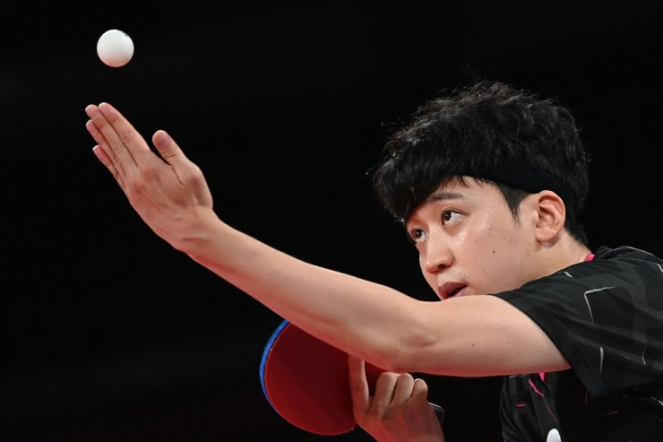 Table tennis player Jeoung Young-sik serves to China's Fan Zhendong during the men's singles quarterfinal table tennis match at the Tokyo Metropolitan Gymnasium in Tokyo, Wednesday. AFP-Yonhap
