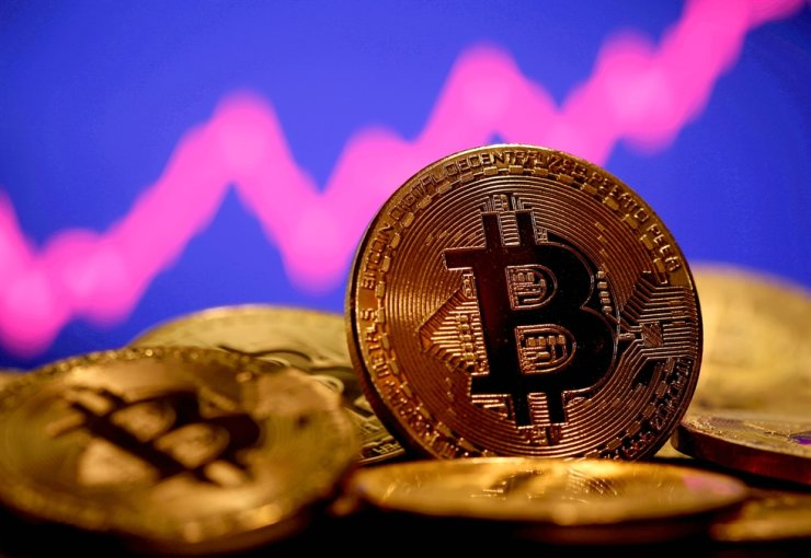 A representation of virtual currency bitcoin is seen in front of a stock graph in this illustration taken Jan. 8. Reuters-Yonhap