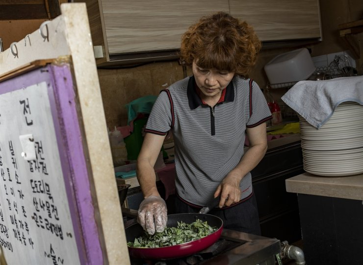 Park makes vegetable jeon (fritter) with locally sourced plants. Korea Times photo by Shim Hyun-chul