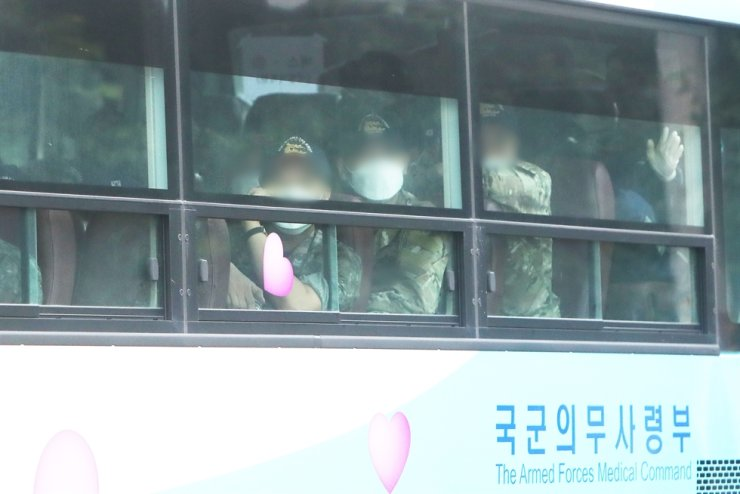 Members of Cheonghae naval unit look out of the windows of a military bus as they are moved to a quarantine facility in Icheon, Gyeonggi Province, from the Seoul Air Base in Seongnam of the province, Tuesday. Yonhap