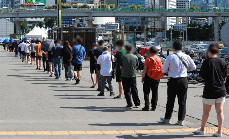 People wait to get tested for COVID-19 at a testing center near Seoul Station in downtown Seoul, July 18. Yonhap
