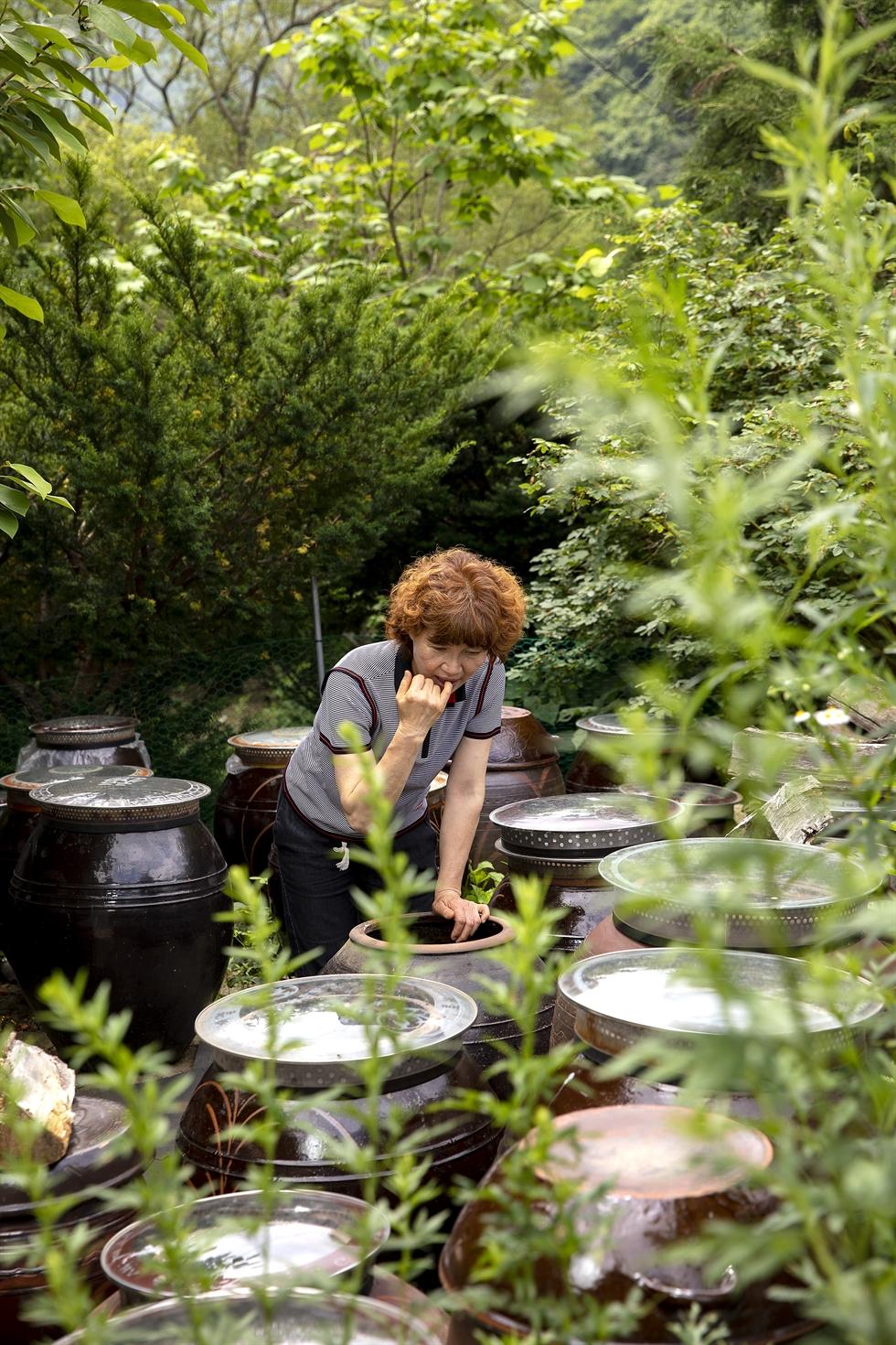 Park tastes her homemade soybean paste in a jar near her home. Korea Times photo by Shim Hyun-chul