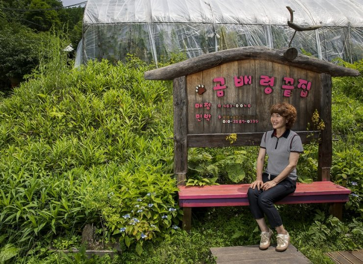 Park So-hee smiles on a bench under a wooden sign for her guesthouse, Gombaeryeong End House, located in Gangwon Province's namesake scenic mountain pass on July 13. Korea Times photo by Shim Hyun-chul
