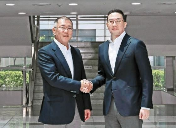 Hyundai Mobis President Cho Sung-hwan, left, holds up an agreement with LG Energy Solution (LGES) President Kim Jong-hyun, after signing a deal with Indonesian officials to invest in a battery joint venture in the Southeast Asian country, at LGES's headquarters in Seoul, Wednesday. On the left screen is Indonesian Minister of Investment Bahlil Lahadalia and on the right screen is Indonesia Battery Corporation CEO Toto Nugroho. Courtesy of LGES