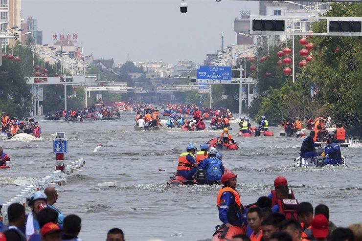 Rescuers use boats to evacuate people from a flooded area in Weihui in central China's Henan Province, July 26. Journalists from several media outlets covering recent floods in China were harassed by local residents, according to the Foreign Correspondents' Club of China. AP-Yonhap