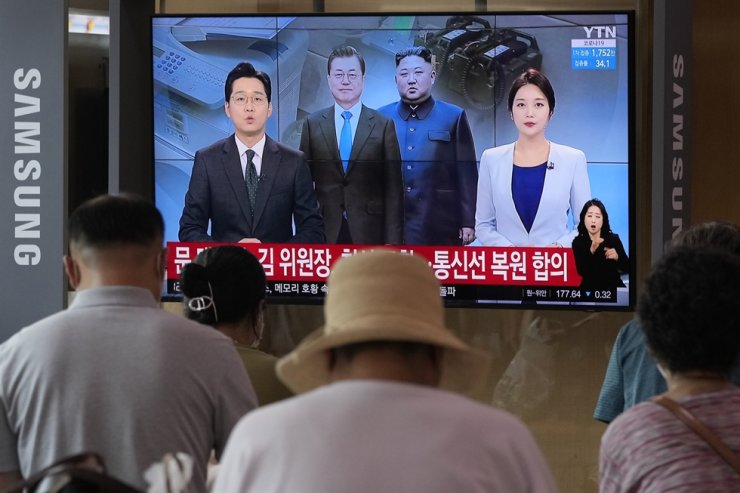 A TV shows a file image of North Korean leader Kim Jong-un and President Moon Jae-in during a news program at the Seoul Railway Station in Seoul, July 27. North Korea reopened its communication channels, including a military hotline, with South Korea on Tuesday (Seoul time). AP-Yonhap