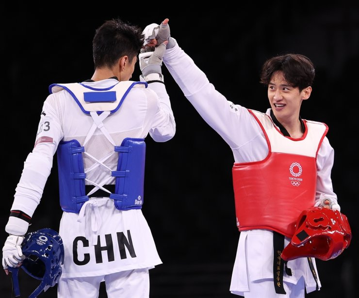 Lee Dae-hoon, right, Korea's taekwondo athlete, congratulates Zhao Shuai of China after losing the match for the bronze medal in the men's 68-kilogram category during the Tokyo Olympics, at Makuhari Messe Hall in Chiba, Japan, Sunday. Yonhap