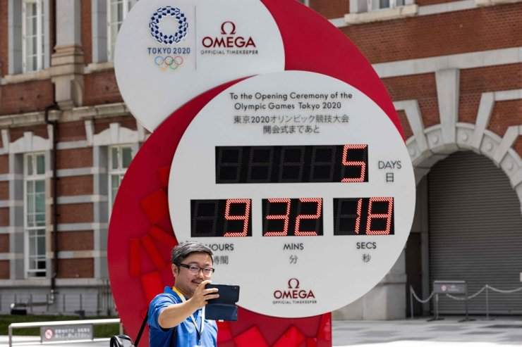 A person takes a picture of the countdown clock for the Tokyo 2020 Olympic Games displaying 5 days and 9 hours to go to the opening ceremony, outside Tokyo station in Tokyo, July 18. AFP-Yonhap
