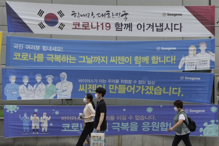 People wearing face masks pass by banners hoping to overcome the COVID-19 crisis on a street in Seoul, July 13. AP-Yonhap