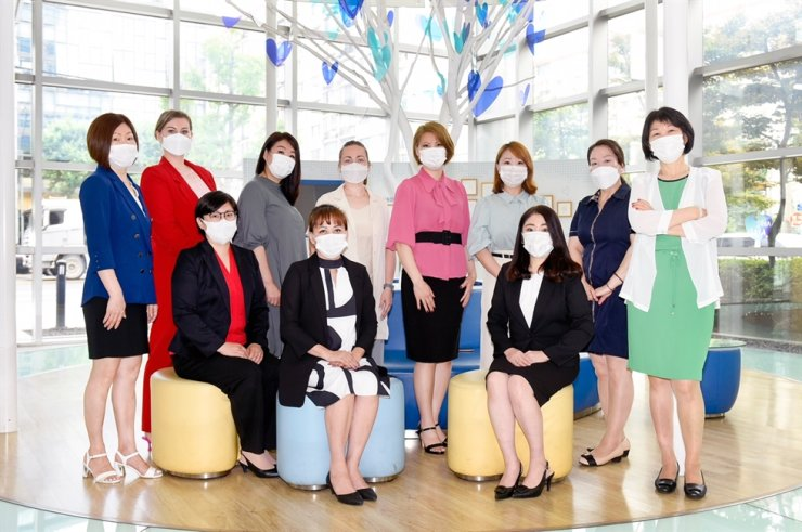 Tsay Tatyana, left in front row, a Samsung Life Insurance sales agent from Uzbekistan, poses with her colleagues at the firm's branch office in Yeongdeungpo, a Seoul district with a large population of foreign residents, July 13. Courtesy of Tsay Tatyana