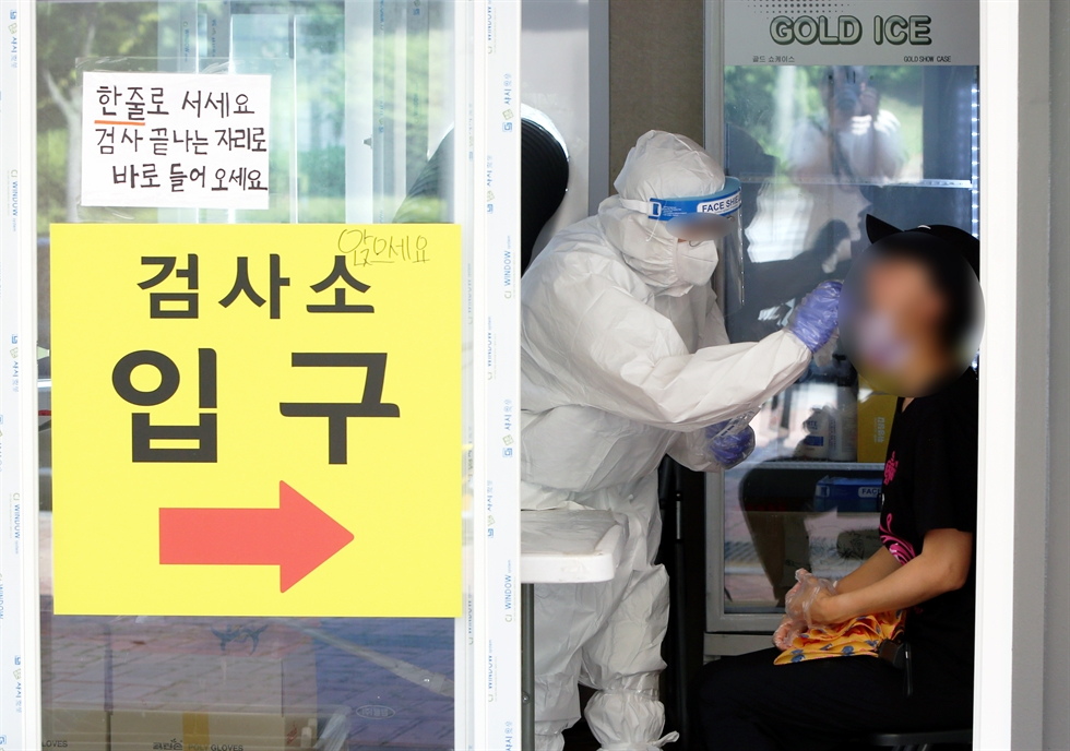 People wait to receive a coronavirus test at a makeshift testing center in Incheon, Wednesday. Yonhap